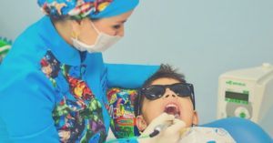 dental hygienist cleaning a child's teeth