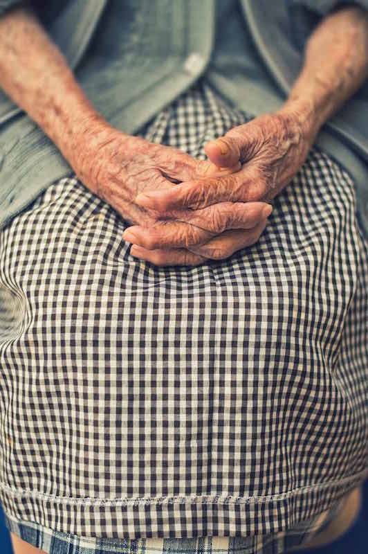 elderly person sitting with hands on their lap