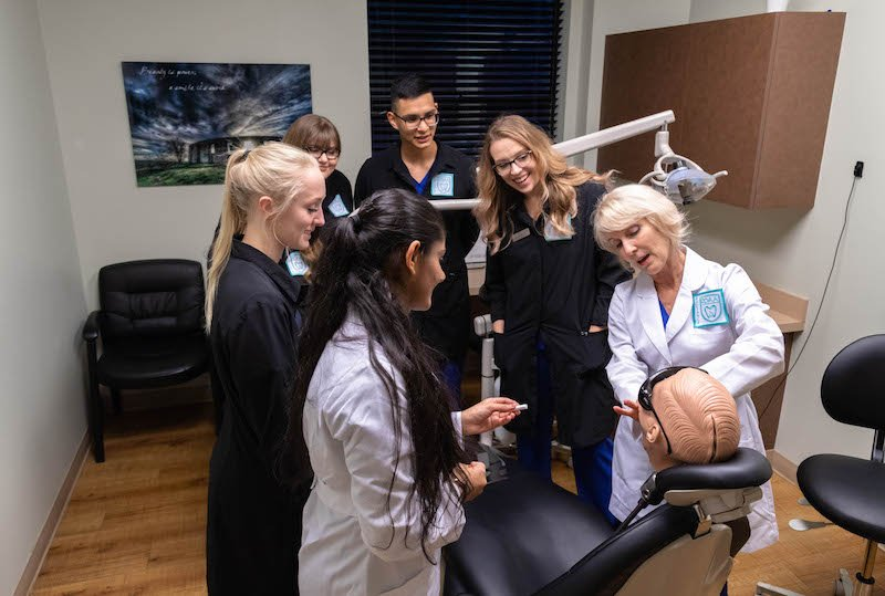 Our head instructor Melanie at Pacific Northwest Dental Assisting School teaching students during class on how to perform assistance as dental assistants. Original Image without tint.