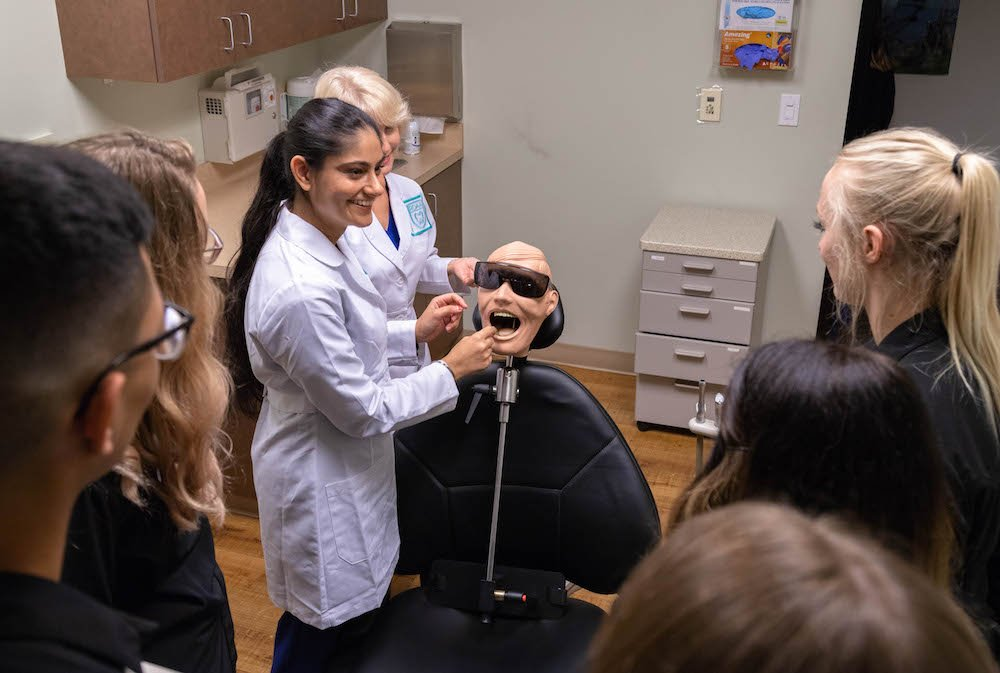 Our experience dental assisting instructor Raj at Pacific Northwest Dental Assisting School teaching students during class on how to perform assistance as dental assistants.